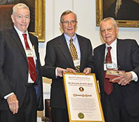 Photograph of Tom Starzl (right) being presented the Franklin Medal by Society President Clyde Barker (left) and Executive Officer Keith Thomson (center).